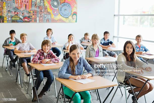 smiling students taking a test in classroom - children only stock pictures, royalty-free photos & images