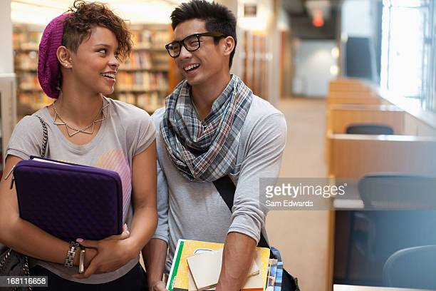 Smiling students talking in library