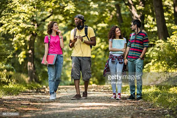 Smiling students walking in nature and talking to each other.