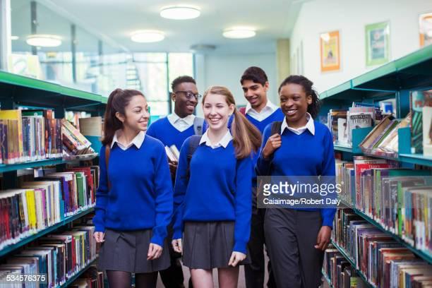 Smiling students wearing blue school uniforms walking between bookshelves in library