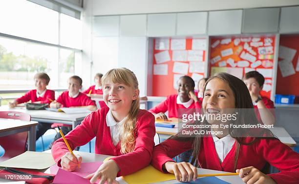 Smiling students writing in classroom