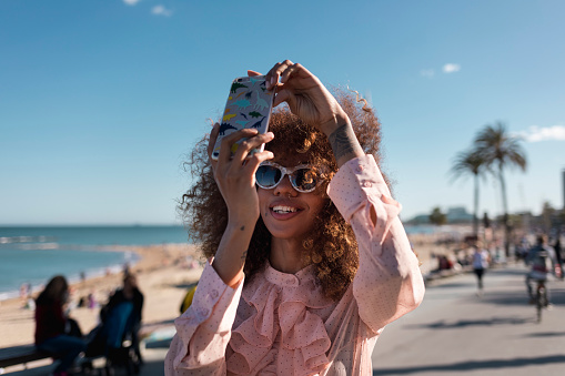 Smiling stylish young woman taking a selfie at seaside promenade - gettyimageskorea
