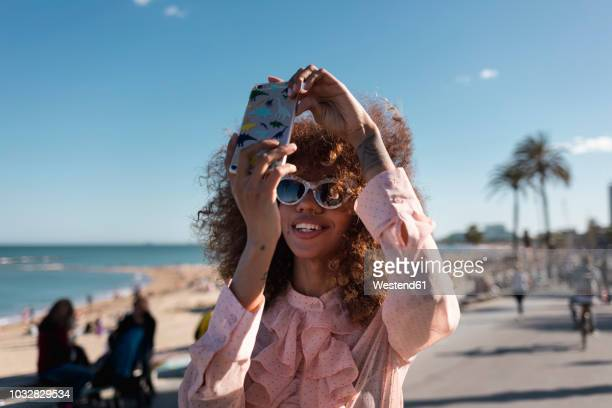 smiling stylish young woman taking a selfie at seaside promenade - mujeres fotos fotografías e imágenes de stock