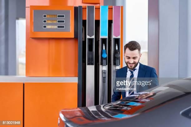 Smiling Successful Businessman Refueling Gas Tank of car in Modern Petrol Station