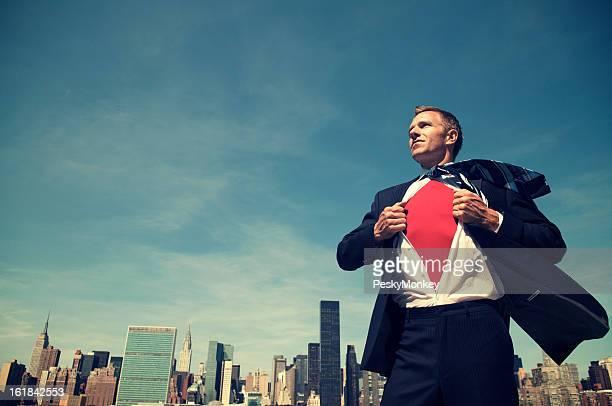 屋外に立って微笑むスーパーヒーローのビジネスマンの街並み