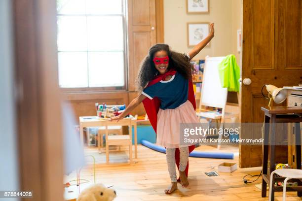 Smiling superhero girl flying in room at home