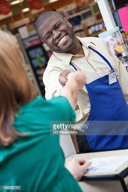 Smiling supermarket worker handing change to customer