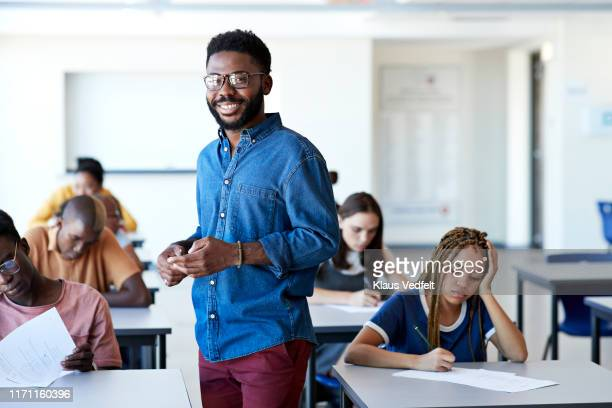 smiling supervisor amidst students writing exam - instructor stock pictures, royalty-free photos & images
