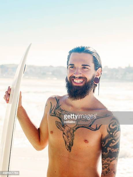 Smiling Surfer holding his surfboard at the beach