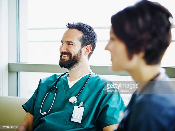 Smiling surgeon in discussion with colleagues