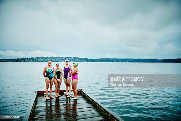 smiling swimmers preparing for morning swim - four people stock pictures, royalty-free photos & images