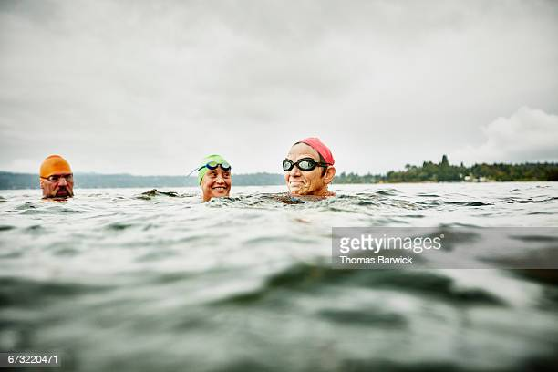 smiling swimmers resting during open water swim - asian 50 to 55 years old woman stock photos and pictures