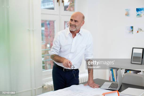 Smiling tattooed businessman in office