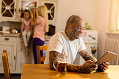 Smiling tattooed man using touchpad in the kitchen.