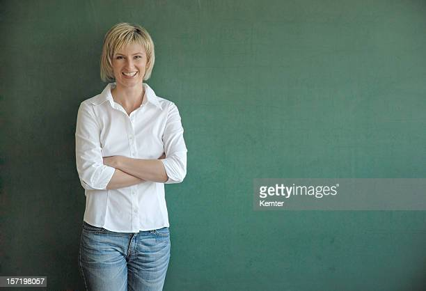 smiling teacher at blackboard - blouse stockfoto's en -beelden