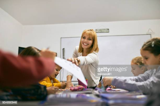 Smiling teacher handing over sheet of paper to student in class