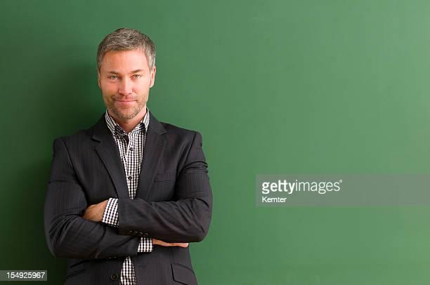 笑顔の先生で、黒板に腕を組む