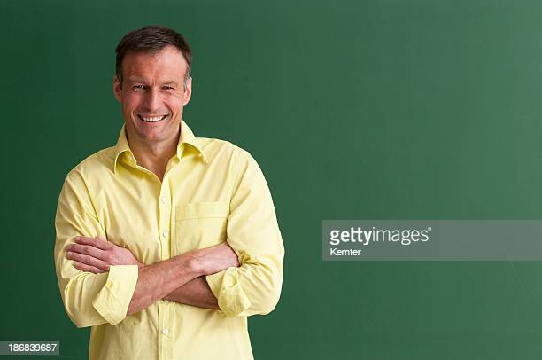 A smiling teacher with arms crossed in front of chalkboard