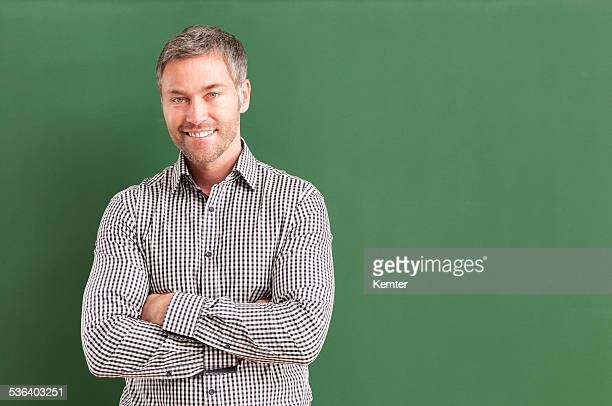 smiling teacher with arms crossed standing at blackboard