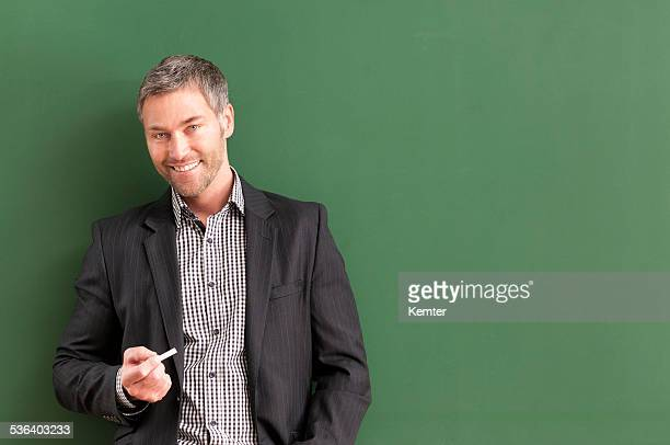 smiling teacher with grey hair at blackboard