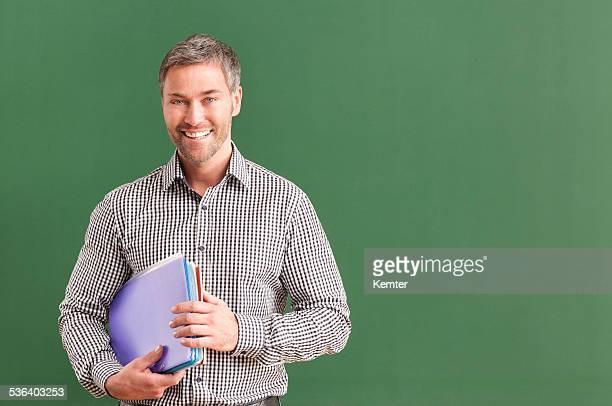 笑顔の先生、灰色のヘアで、黒板