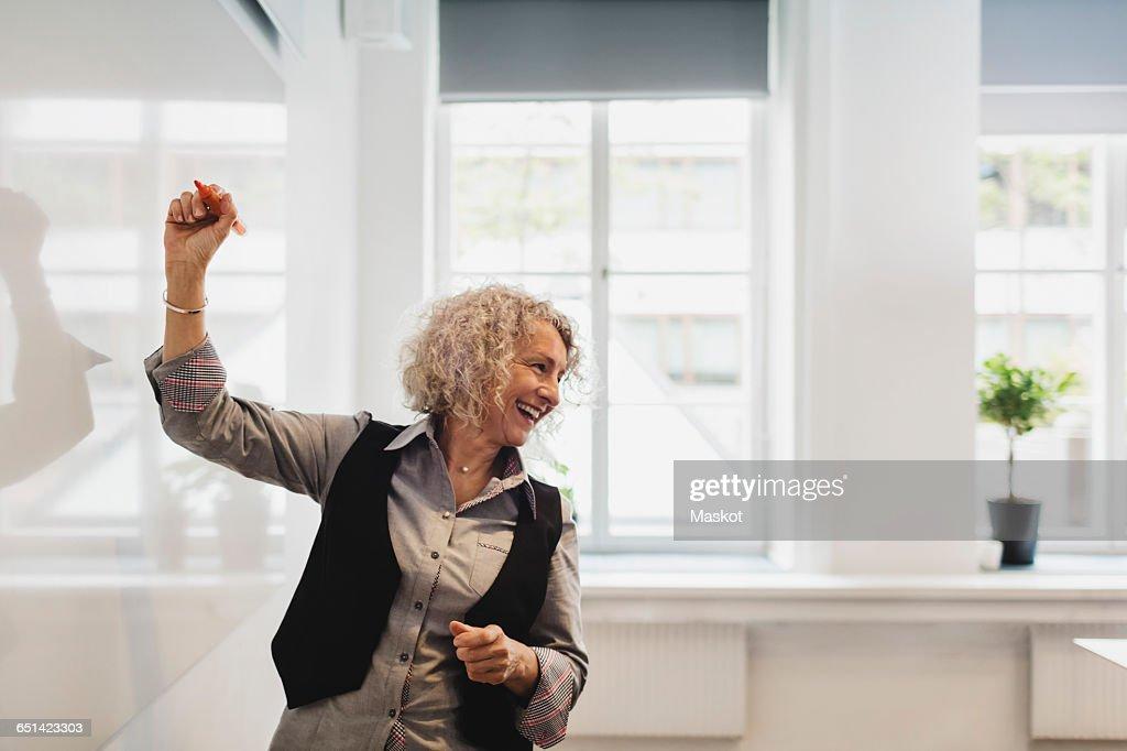 Smiling teacher writing on whiteboard in language class : Stock Photo