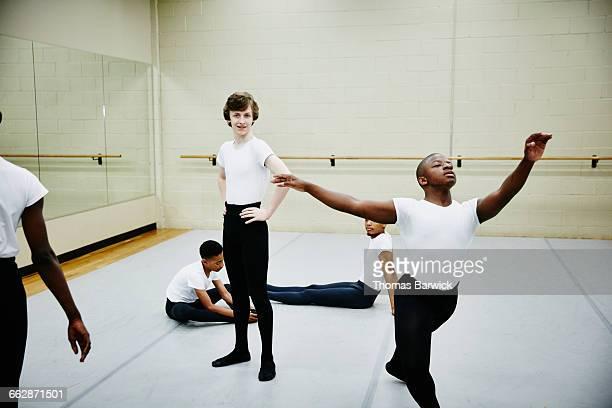 Smiling teen ballet dancers warming up in studio