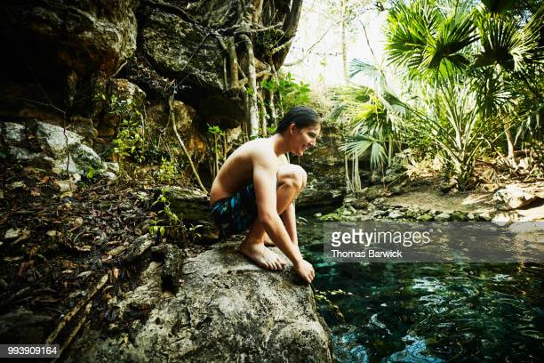 Smiling teen boy resting on rock after swimming in cenote during vacation