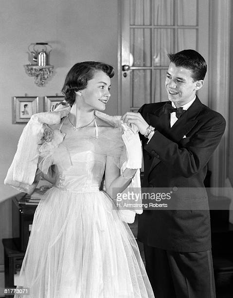 Smiling Teen Couple Girl In Prom Gown & Boy In Tux Putting Shawl Over Her Shoulders.