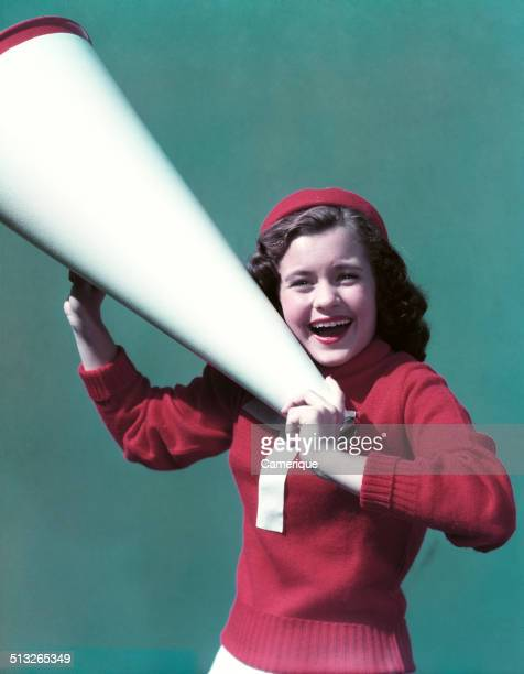 Smiling teen girl cheerleader wearing varsity letter sweater holding megaphone, Los Angeles, California, 1949.