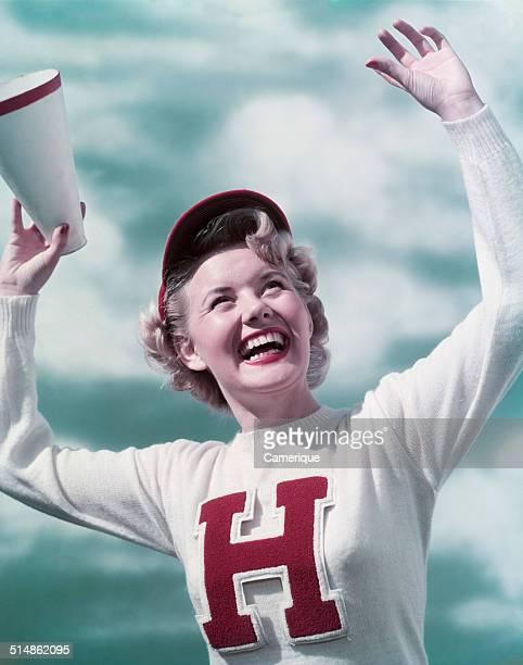 Smiling teen girl cheerleader wearing varsity letter sweater holding megaphone arms raised cheering, Los Angeles, California, 1949.