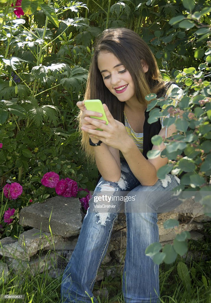 Smiling teen girl in beautiful garden, on her smart phone. : Stock Photo
