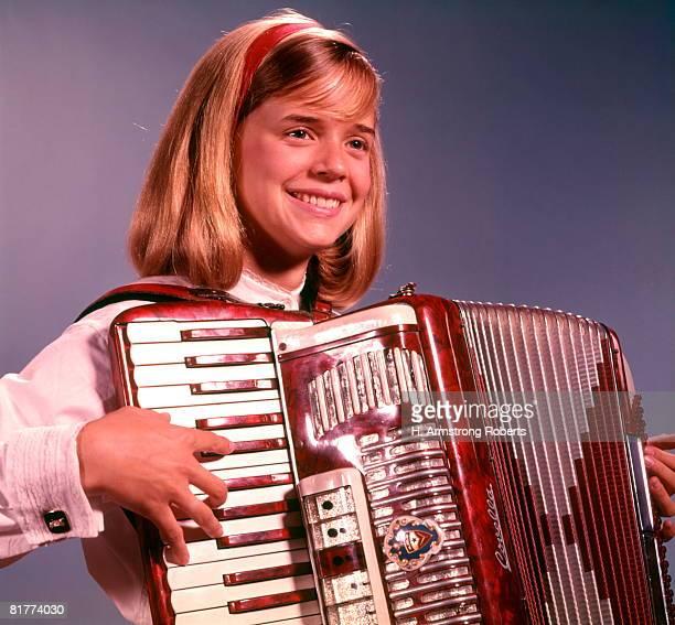 Smiling teen girl, playing accordion.
