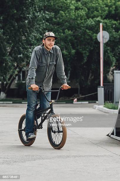 Smiling teenage boy cycling at skateboard park
