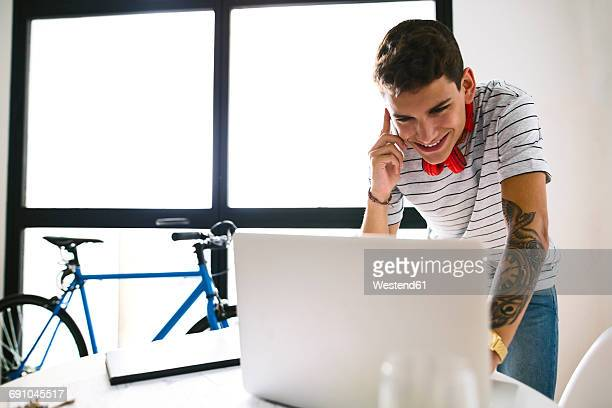 Smiling teenage boy on the phone looking at laptop