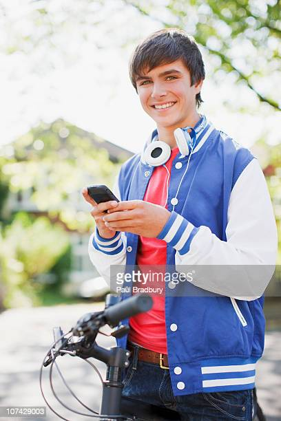 Smiling teenage boy with bicycle text messaging on cell phone