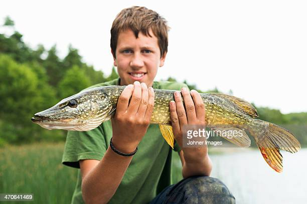 smiling teenage boy with caught fish - pike fish stock pictures, royalty-free photos & images