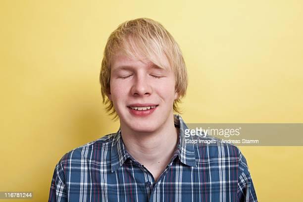 A smiling teenage boy with eyes closed, portrait, studio shot