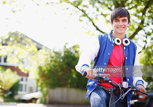 sorridente menino adolescente com auscultadores e bicicleta - só meninos adolescentes imagens e fotografias de stock