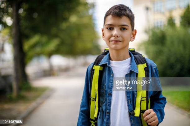 smiling teenage boy with school bag in front of school - boys stock pictures, royalty-free photos & images