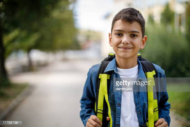 smiling teenage boy with school bag in front of school - school child stock pictures, royalty-free photos & images