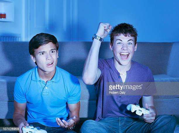 Smiling teenage boys playing video game