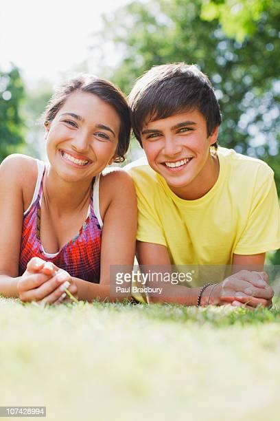 Jeune couple souriant en herbe ensemble de l'établissement
