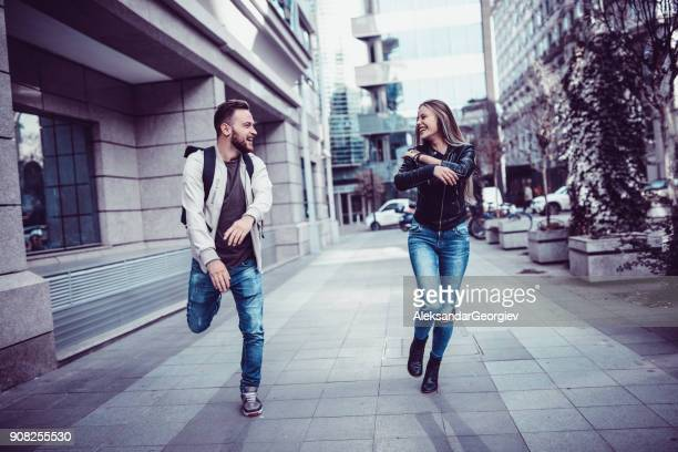 Smiling Teenage Couple Walking and Jumping in the City Street