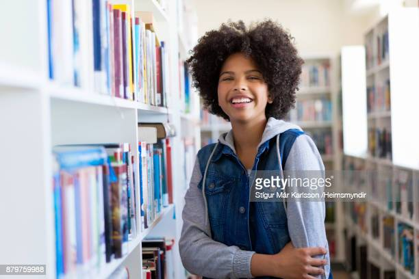 Smiling teenage female student in library