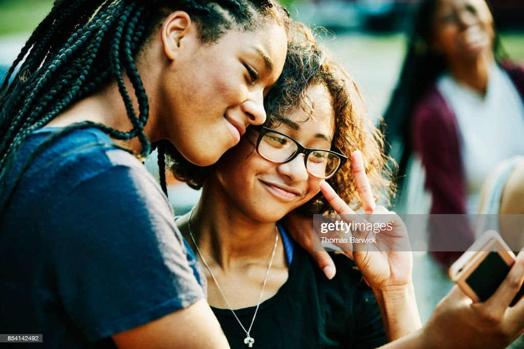 Smiling teenage friends taking selfie with smartphone on summer evening : Stock Photo