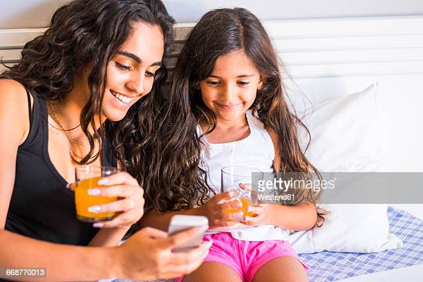 Smiling teenage girl and her little sister with juice glasses and cell phone