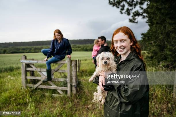 smiling teenage girl and wet dog on weekend hike with family - sibling stock pictures, royalty-free photos & images