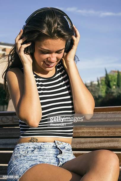 smiling teenage girl hearing music with headphones - alleen tienermeisjes stockfoto's en -beelden