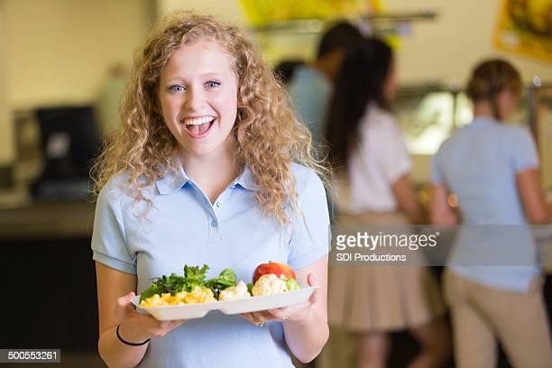 Glücklich high-school-Mädchen hält Teller mit gesunden cafeteria Speisen